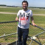 Ekrem staat met een taststok op een verhoging, bij Luchtvaartmuseum Aviodrome in Lelystad. Achter hem de start- en landingsbaan van luchthaven Lelystad