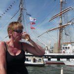 Petra drinkt witte wijn uit een plastic bekertje. Zij vaart samen met andere doofblinde mensen in een boot. Georganiseerd door Doofblinden in Beweging, tijdens SAIL 2010.