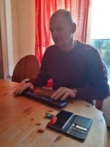 Louis gebruikt een brailleleesregel, samen met een telefoon
