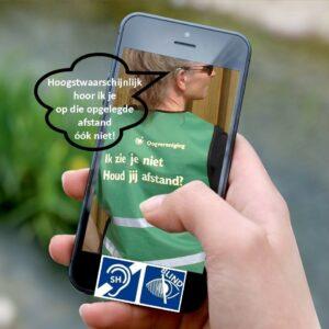 Beeld in mobiele telefoon: Ans draagt een groen hesje met tekst op de achterzijde: Ik zie je niet. Houd jij afstand? In een tekstballon bij haar rechteroor de tekst: Hoogstwaarschijnlijk hoor ik je op die opgelegde afstand óók niet! Aan de onderzijde van de telefoon twee logo's: links het logo Slechthorend, rechts het logo Blind.